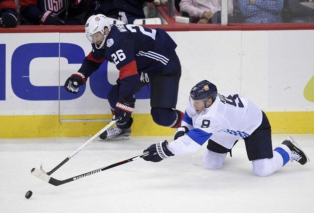 Fin Mikko Koivu (vpravo) A Američan Blake Wheeler v souboji o puk.