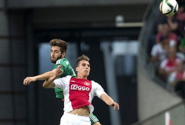Útočník Ajaxu Arkadiusz Milik (vpředu) v souboji s Thanosem Petsosem z Rapidu Vídeň v odvetě 3. předkola Ligy mistrů.