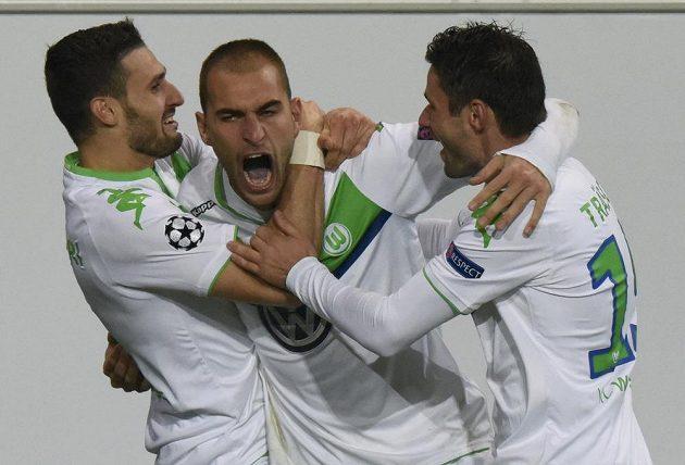 Nizozemský útočník Bas Dost (uprostřed) ve službách Wolfsburgu se raduje z trefy v utkání Ligy mistrů proti PSV Eindhoven. Vlevo Daniel Caliguri, vpravo Christian Traesch.
