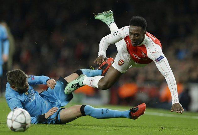 Barcelonský stoper Gerard Piqué v tvrdém střetu s Dannym Welbeckem z Arsenalu.