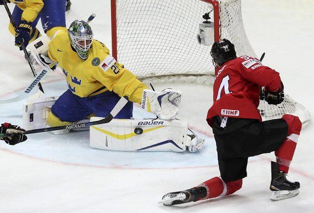Švýcar Samuel Walser zkouší vyzrát na švédského gólmana Jacoba Markströma.