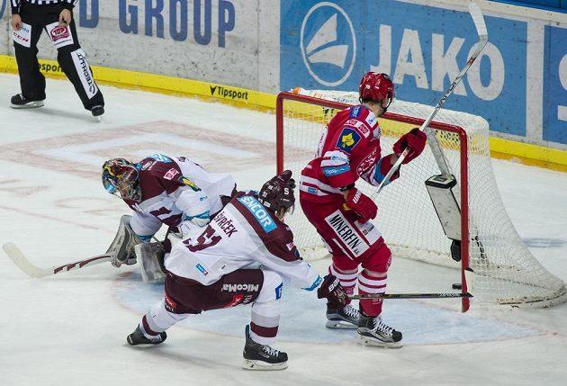 Útočník Třince Lukáš Žejdl (vpravo) střílí gól. V brance Sparty je Tomáš Pöpperle, uprostřed obránce Jan Švrček.