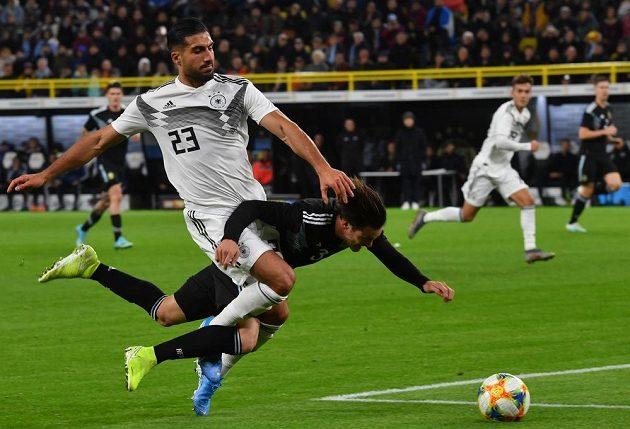 Němec Emre Can (vlevo) a Argentinec Nicolas Tagliafico v souboji během přípravného utkání.