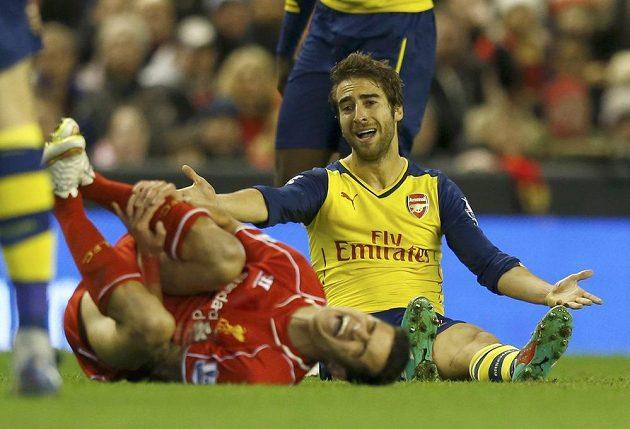 Liverpoolský Philippe Coutinho (vlevo) se svíjí na trávníku po zákroku záložníka Flaminiho z Arsenalu.
