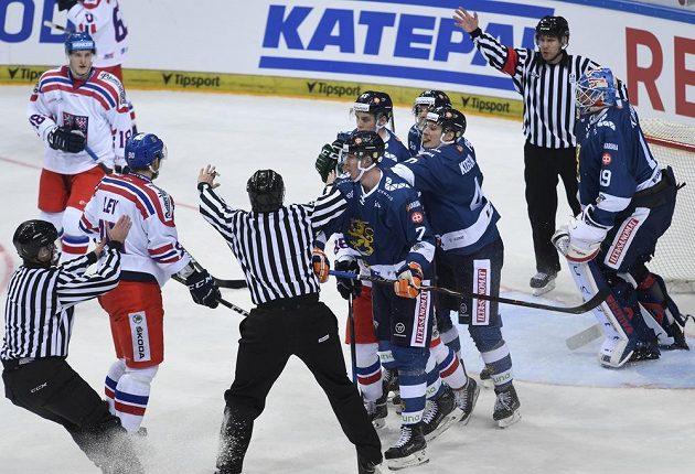Rozhodčí uklidňují hráče před finskou brankou.