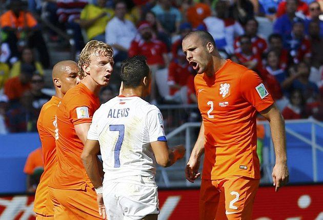 Nizozemští obránci Dirk Kuijt a Ron Vlaar (2) v ostré diskuzi s Alexisem Sanchézem z Chile.