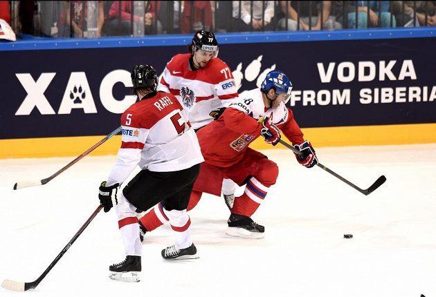 Jaromír Jágr proti dvojici rakouských hokejistů Thomasi Rafflovi (č.5) a Florianovi Muhlsteinovi.