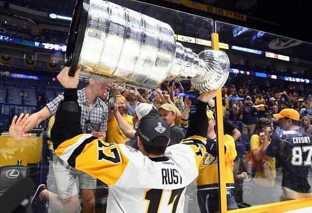 Pravé křídlo hokejového Pittsburghu Penguins Bryan Rust slaví se Stanley Cupem nad hlavou na ledě Nashvillu Predators.