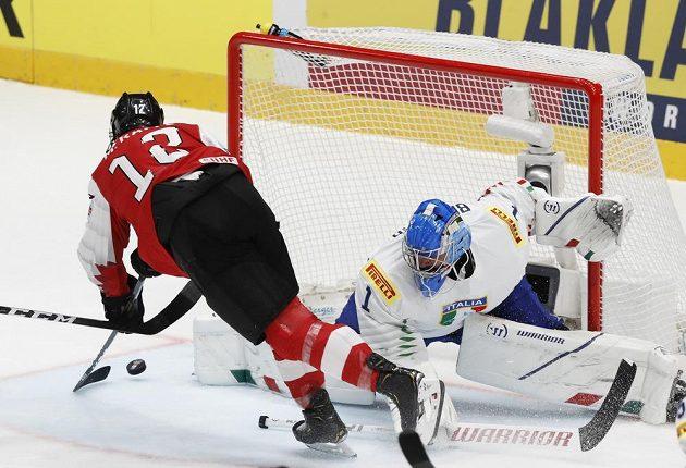 Rakouský hokejista Michael Raffl dává gól do sítě italského gólmana Andrease Bernarda.