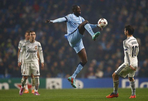 Záložník Manchesteru City Yaya Toure (uprostřed) zpracovává míč před Alanem Dzagojevem z CSKA Moskva.