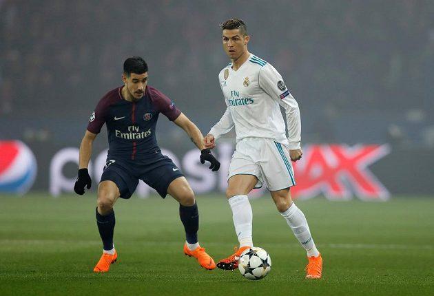 Cristiano Ronaldo z Realu Madrid odehrává míč v utkání s PSG. Akci přihlíží hráč francouzského týmu Yuri Berchiche.