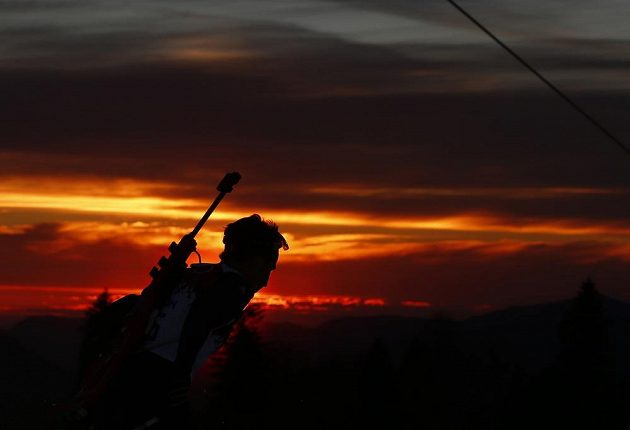 Silueta Oleho Einara Björndalena proti západu slunce při vytrvalostním závodu biatlonistů.