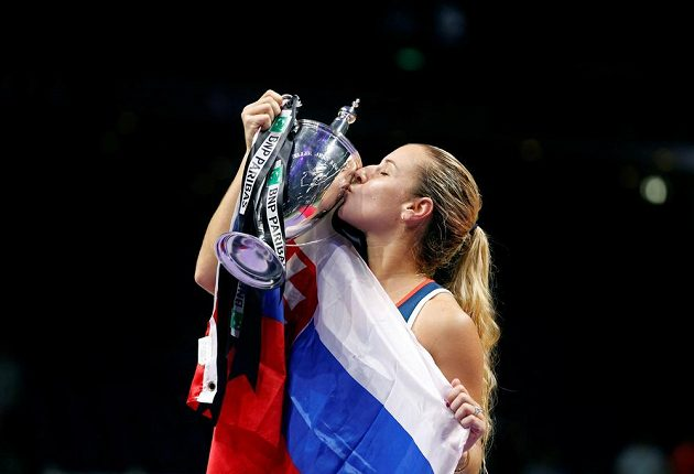 Štastná Dominika Cibulková zabalena do vlajky Slovenska líbá kýžený pohár.