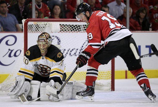 Brankář Bostonu Tuukka Rask kryje puk před Jonathanem Toewsem z Chicaga během druhé třetiny úvodního finále Stanley Cupu.