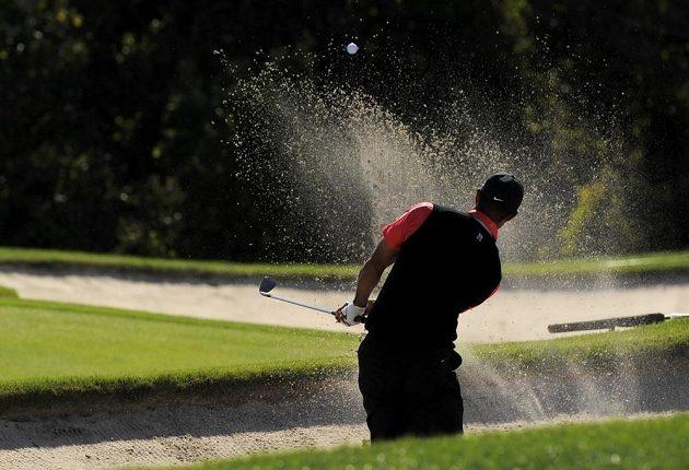 Tiger Woods zahrává míček z písku