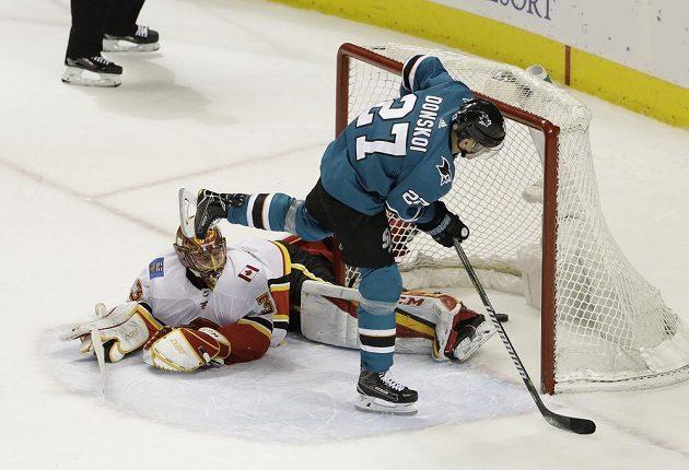 Joonas Donskoi (27) ze San Jose překonává Davida Ritticha v brance Calgary při samostném nájezdu v utkání NHL.