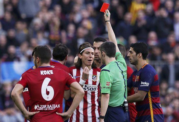 Obránce Atlétika Madrid Filipe Luís dostává po faulu na Lionela Messiho červenou kartu.