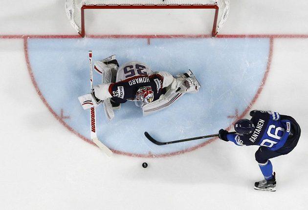Finský hokejista Mikko Rantanen v akci před americkým gólmanem Jimmy Howardem. Fin z této akce vstřelil úvodní gól zápasu.