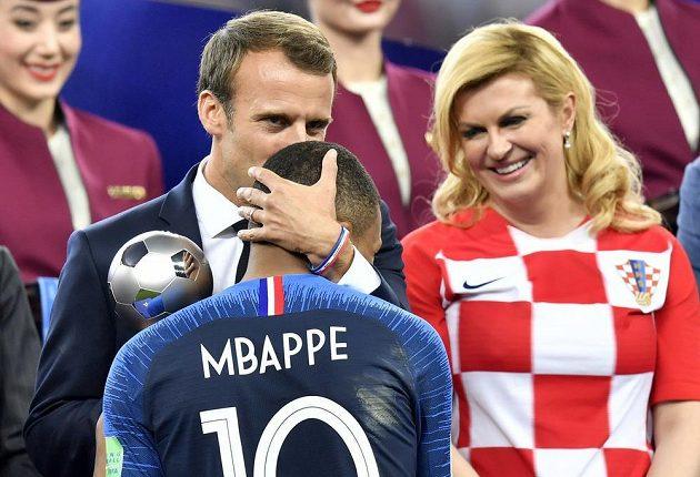Francouzský prezident Emmanuel Macron za dohledu chorvatské prezidentky Kolindy Grabarové-Kitarovičové objímá Kyliana Mbappého.