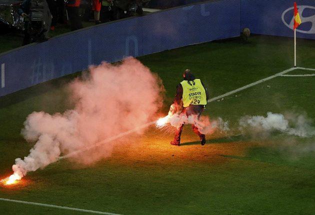Stewardi uklízí světlice na hrací ploše během utkání Česka s Tureckem.
