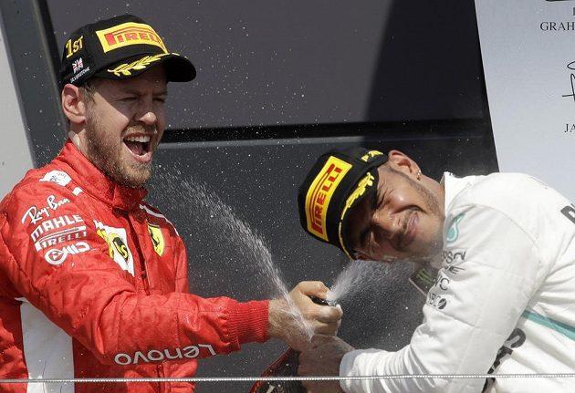 Vítězný Němec Sebastian Vettel (vlevo) a druhý Brit Lewis Hamilton po závodě v Silverstonu.