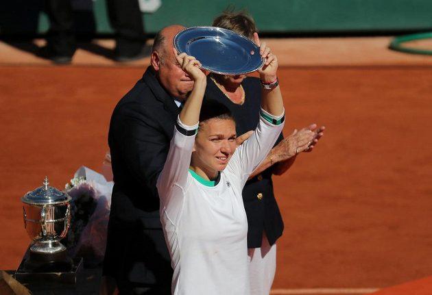 Simona Halepová zvedá nad hlavu talíř, který je určen pro poraženou finalistku Roland Garros.