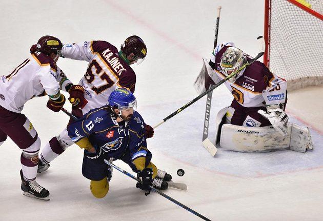 Kladenský Ladislav Zikmund padá na led v utkání 50. kola první hokejové ligy v Jihlavě. Zikmunda atakovali zleva Nicolas Werbik a David Kajínek z Jihlavy. Vše sleduje gólman Jihlavy David Honzík.