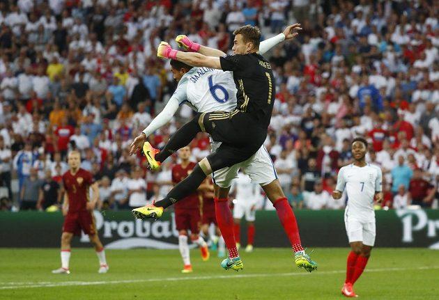 Ruský brankář Igor Akinfejev vyboxoval míč těsně před dorážejícím obráncem Anglie Chrisem Smallingem v zápase mistrovství Evropy.