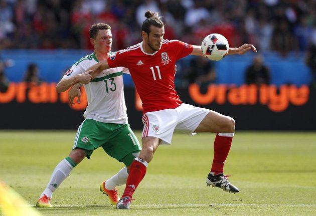 Velšana Garetha Balea (vpravo) brání Corry Evans ze Severního Irska.