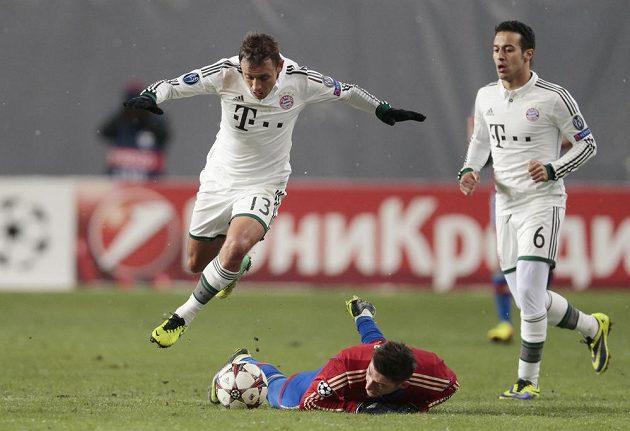Obránce Bayernu Mnichov Rafinha se snaží obejít Stevena Zubera z CSKA Moskva. Vpravo přihlíží Thiago Alcantara z Bayernu.