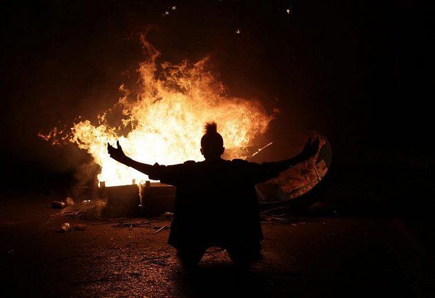 Demonstrant klečí před zapálenou barikádou v Rio de Janeiru.
