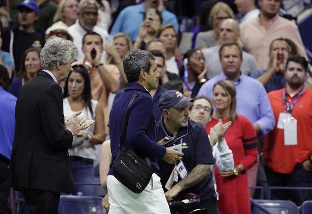 Umpirový sudí Carlos Ramos (vpravo) odchází do útrob stadiónu Arthura Ashe.
