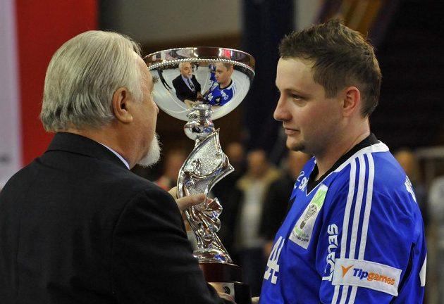 Házenkář Hranic Tomáš Galus přebírá trofej pro vítěze Českého poháru.