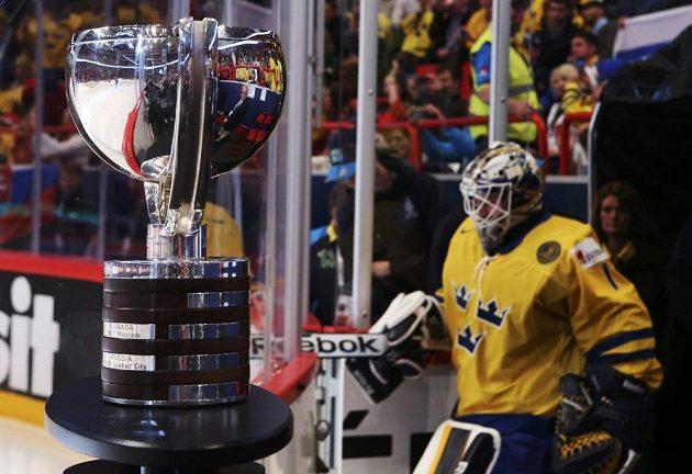 Vpředu se blyští trofej pro mistry světa. V pozadí nastupuje švédský brankář Enroth do finálového utkání.
