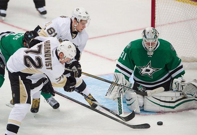 Útočník Pittsburghu Patric Hörnqvist se snaží překonat brankáře Dallasu Anttiho Niemiho. Vzadu přihlíží forvard Penguins Sergej Plotnikov.
