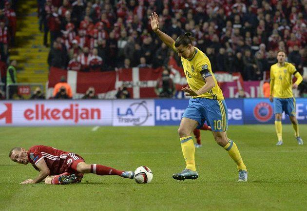 Thomas Kahlenberg (vlevo) z Dánska se i vleže snaží zabránit ve střelbě švédskému kanonýrovi Zlatanu Ibrahimovicovi.