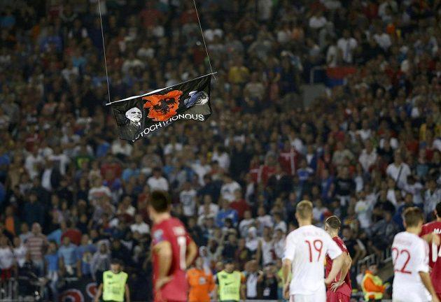 Fotbalisté Srbska a Albánie se dívají na vlajku, která se vznáší nad trávníkem.