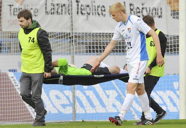 Zraněného ostravského brankáře Jiřího Pavlenku (na nosítkách) doprovází ze hřiště jeho spoluhráč Michal Frydrych.