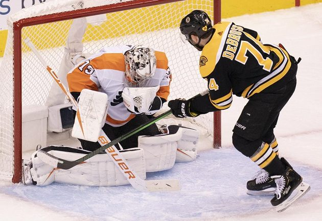 Gólman Philadelphie Flyers Carter Hart (79) zneškodnil šanci útočníka Bostonu Bruins Jakea DeBruska (74).