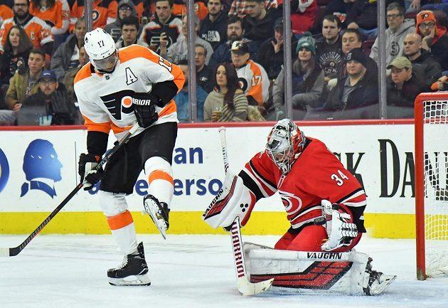 Útočník Philadelphie Wayne Simmonds se snaží nachytat v utkání NHL brankáře Caroliny Hurricanes Petra Mrázka. Tentokrát se mu to nepovedlo.