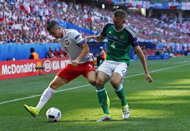 Polský kanonýr Robert Lewandowski (vlevo) si kryje míč před Garethem McAuleyem ze Severního Irska.