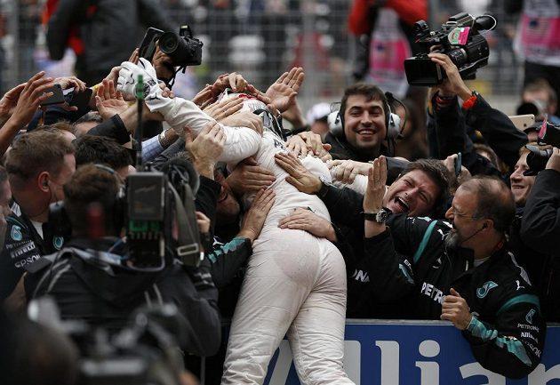 Lewis Hamilton v objetí svého týmu krátce po vítězství ve Velké ceně USA.