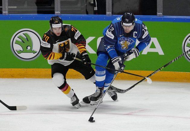 Kapitán finských hokejistů Marko Anttila (vpravo) si kryje puk před německým útočníkem Johnem Peterkou.