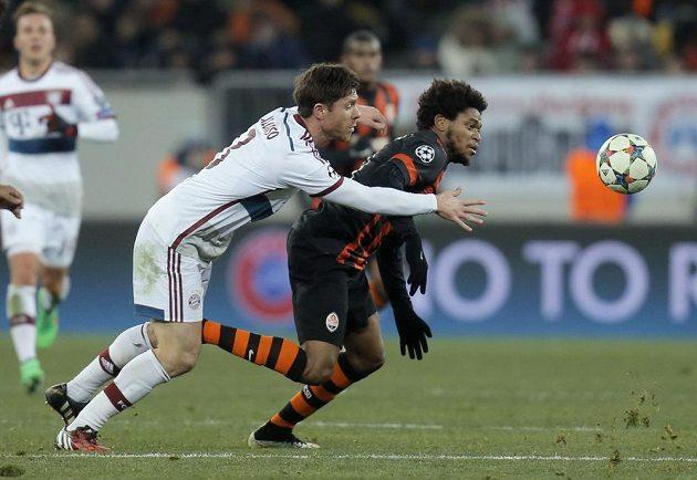 Záložník Bayernu Xabi Alonso (vlevo) se snaží zastavit Luize Adriana z Šachtaru v prvním osmifinálovém utkání Ligy mistrů.