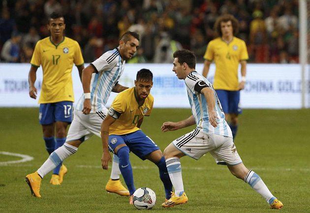 Argentinský kapitán Lionel Messi prochází okolo Brazilce Neymara, který v přátelském zápase v Pekingu rovněž navlékl kapitánskou pásku.
