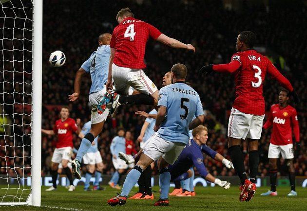 Obránce Manchesteru United Phil Jones (4) namířil svou hlavičku do zad Vincenta Kompanyho z Manchesteru City, od kterého se míč odrazil za brankovou čáru.