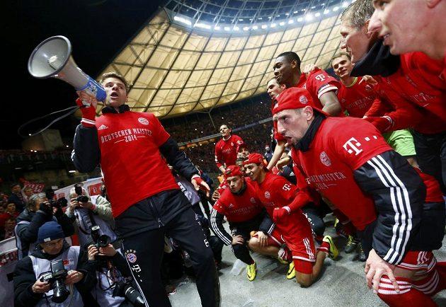 Útočník Thomas Müller byl lídrem mistrovských oslav Bayernu Mnichov - vlevo s megafonem v ruce promlouvá k vlastním fanouškům.