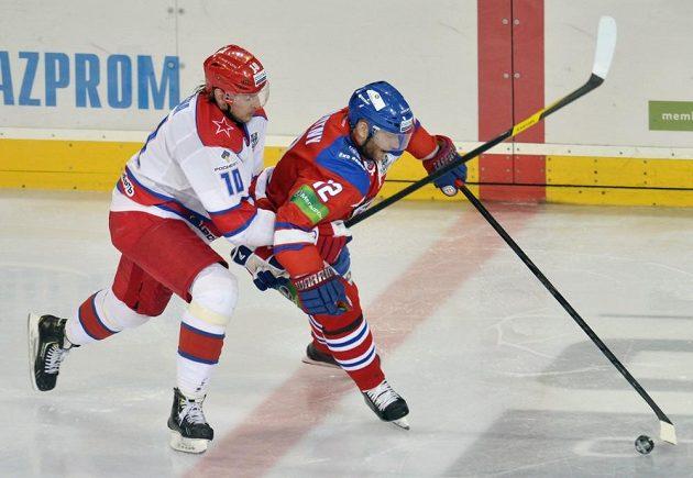 Jiří Novotný (vpravo) ze Lva Praha si kryje puk před dotírajícím Olegem Kvašou z moskevského CSKA.