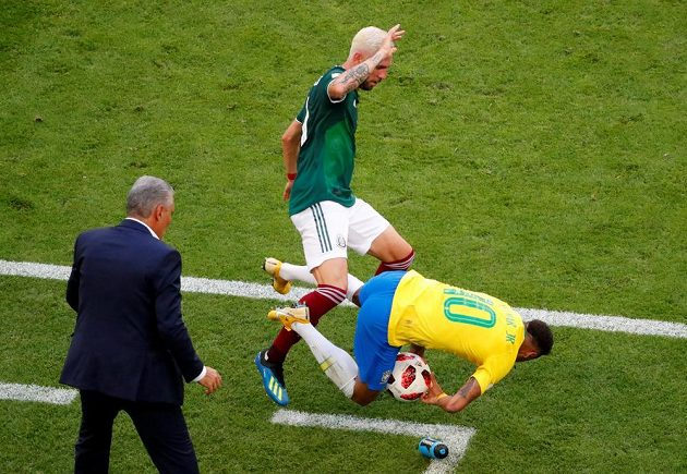 Brazilský útočník Neymar padá po kontaktu s mexickým obráncem Layúnem, který mu chce vypíchnout míč, jenž Neymar drží v náručí.