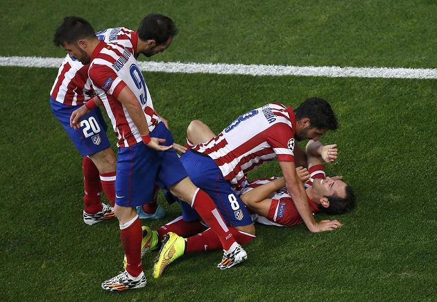 Střelec gólu Atlétika Diego Godín (na zádech) jásá se spoluhráči.